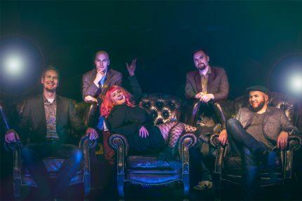 Bilebändi Gringon promokuva 2018 jossa kolme muusikoista istuu nahkatuoleilla naureskellen ja kaksi seisoskelee takana mietteliään oloisina