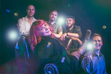 Bilebändi Gringon promokuva 2018 jossa solisti Emma istuu nahkatuolilla hymyillen soittajapoikien ympäröimänä